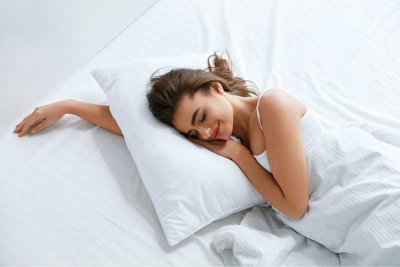 Frau liegt auf einem weissen Kissen