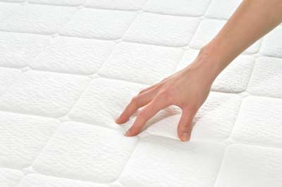 Hand streicht ueber eine weisse Matratzenauflage von Sweet Dreams