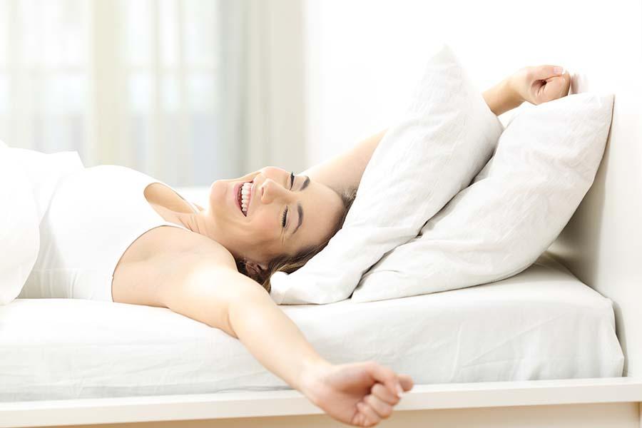 Frau wacht auf und streckt sich glücklich in ihrem Bett
